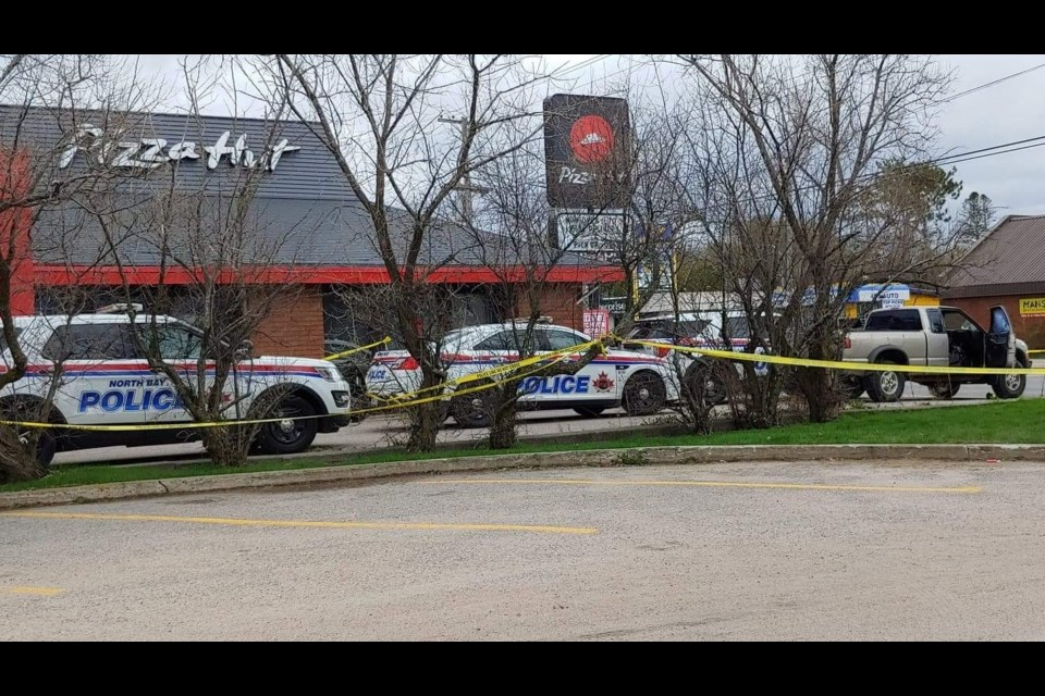 Police vehicles surrounded a pickup truck in the parking lot of Pizza Hut on Lakeshore Drive.