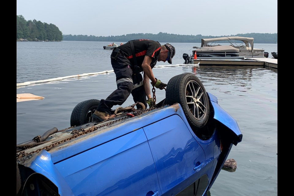 Larry Bartlett, owner of Bartlett's Towing puts hooks underneath the carriage of a car that smashed through a guard rail and into Trout Lake.  Photo by Chris Dawson/BayToday.