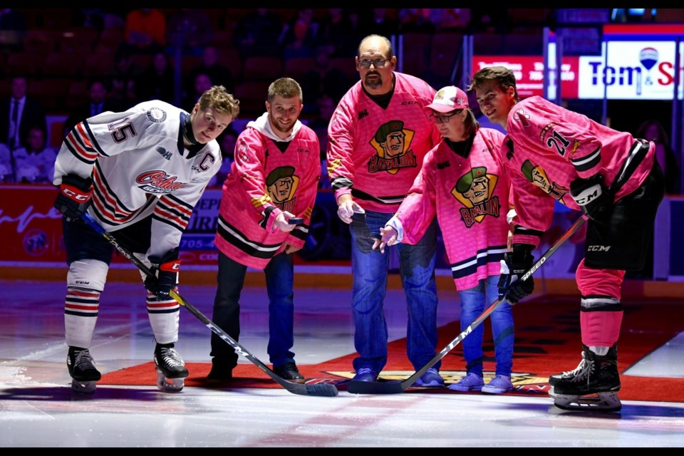 Brandon Coe and his father Lance take part in the Ceremonial Puck Drop. Photo courtesy Tom Martineau.