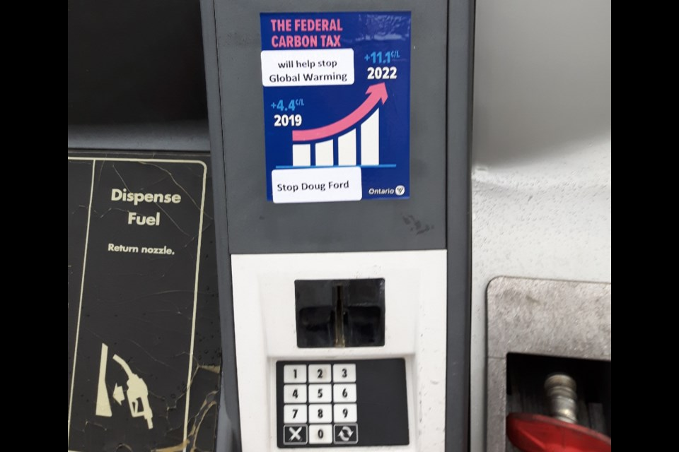 Someone is putting stickers on top of the usual gas pump carbon tax decals. Supplied.