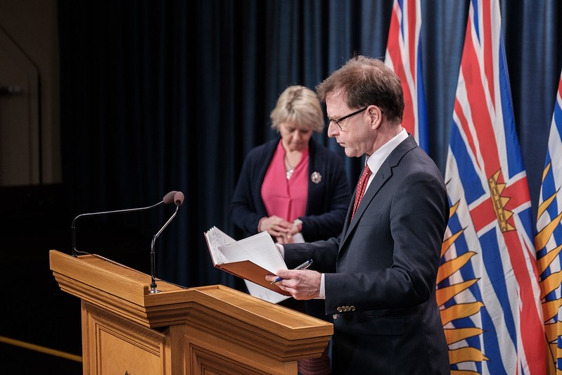 Adrian Dix with Bonnie Henry at podium