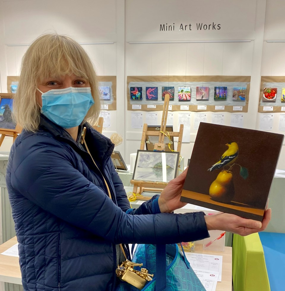 Woman holding a painting of a bird sitting on a pear
