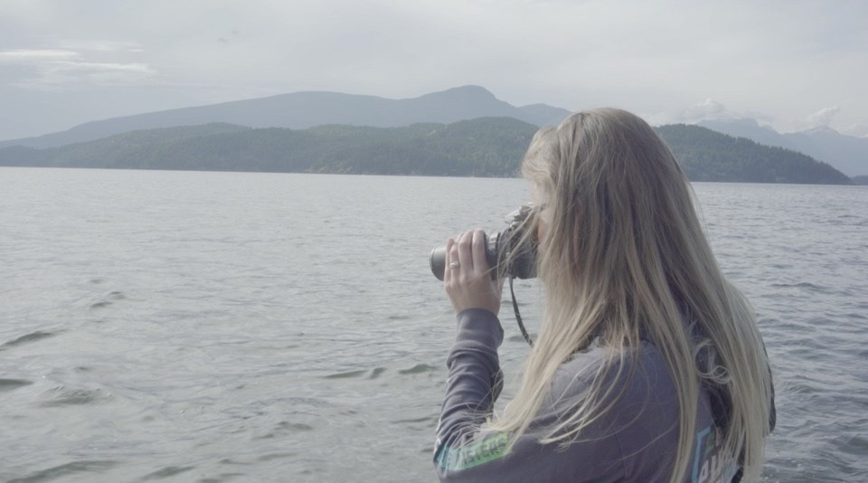 A woman looking through binoculars out at Howe Sound