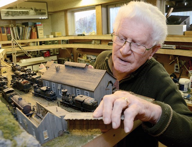 """Rob Wynen clipped this photo out of the North Shore News back in 2014, with the intention of calling up Bob Booth. The original caption: """"North Vancouver model railroad enthusiast inspects one of the buildings in his train station."""""""