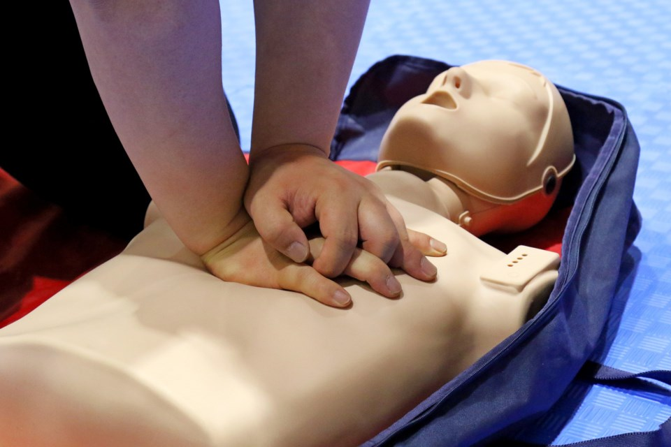 forearms and hands of someone doing CPR on dummy