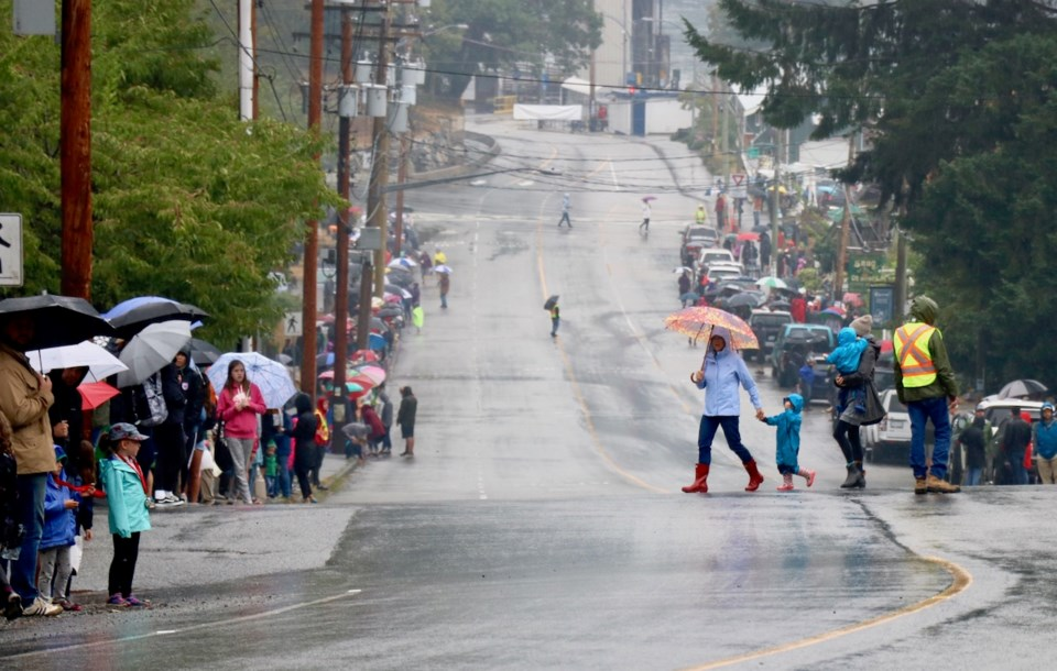 A woman holding the hand of a child as they cross the street during the pouring rain of Bowfest 2018