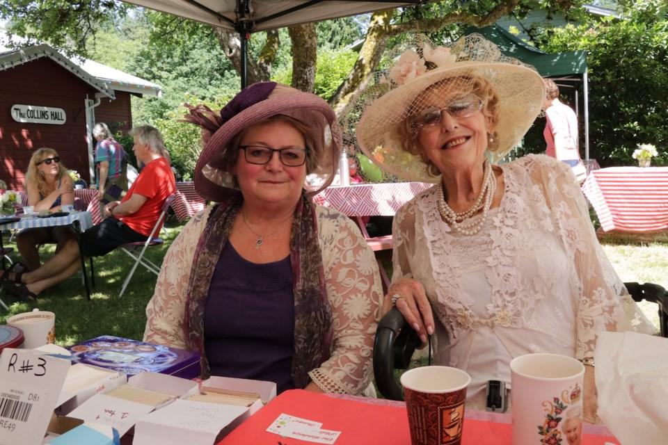 Two women in fancy tea outfits outside