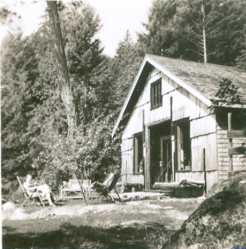 Black and white photograph of two people sitting outside of a barn-looking building in the woods