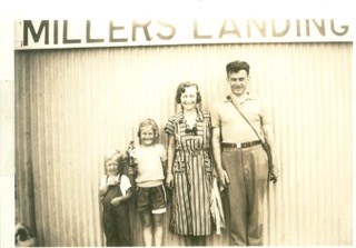 Two adults and a child standing beneath a Millers Landing sign