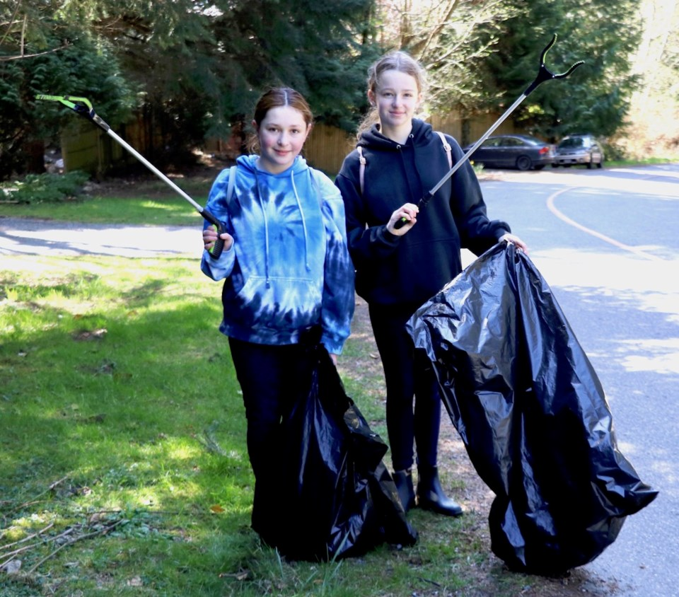 Ela and Hadley hold up their trash pickers
