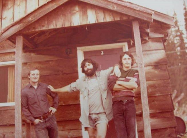 Three men standing in front of a rustic-looking cabin in 1970s