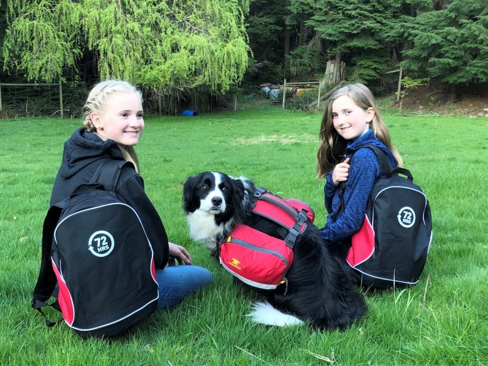 Two girls and a dog wearing emergency preparedness backpacks