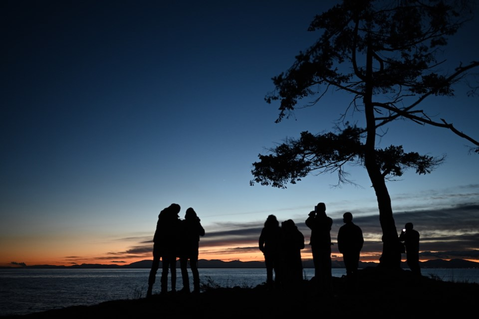 Silhouettes of people standing at the Cape at sundown