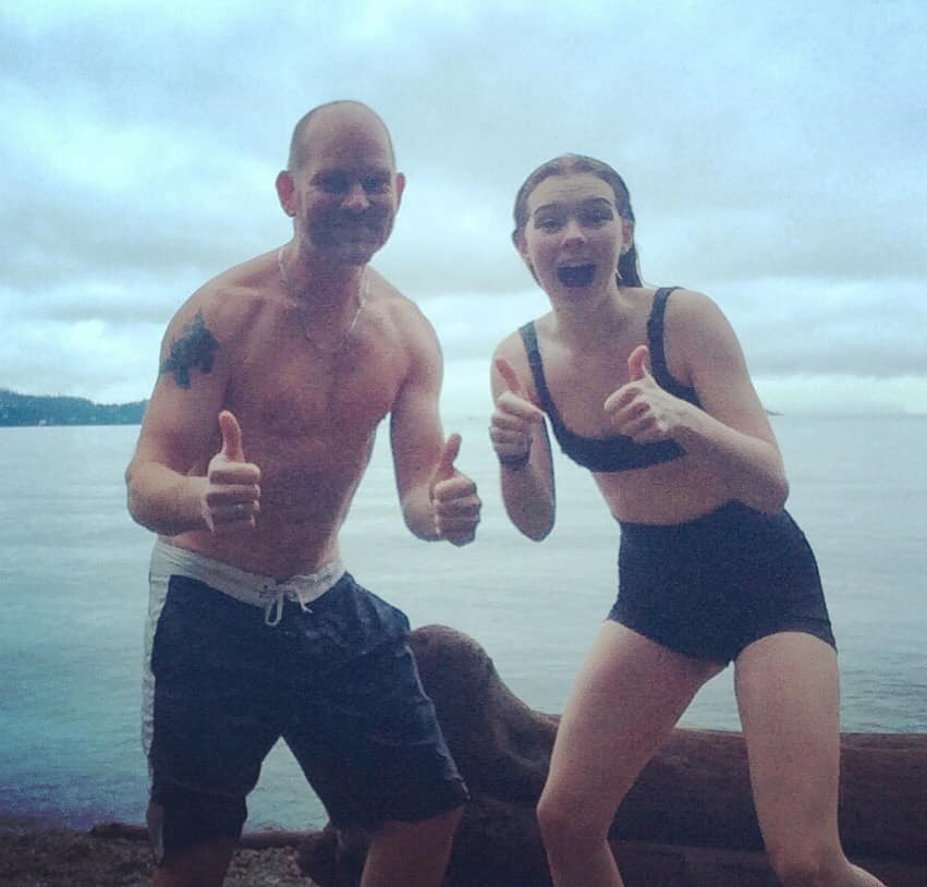 Father and daughter in swimsuits on the beach giving thumbs up