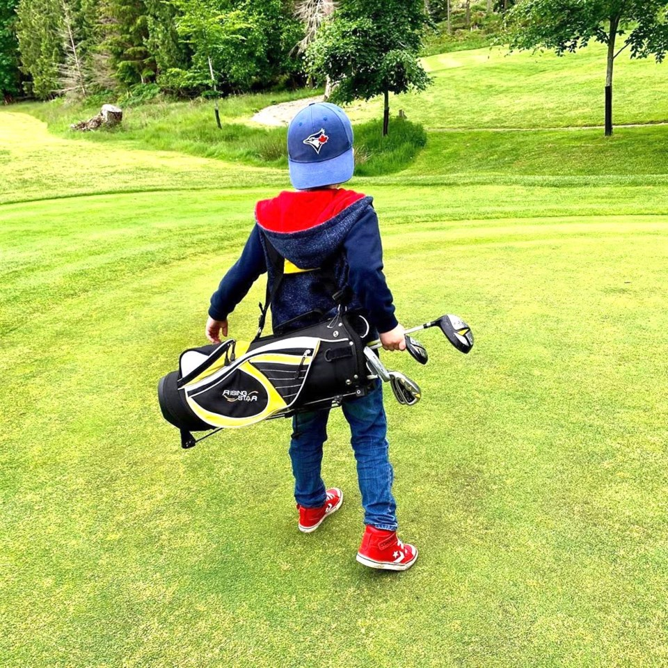 Kid with golf clubs
