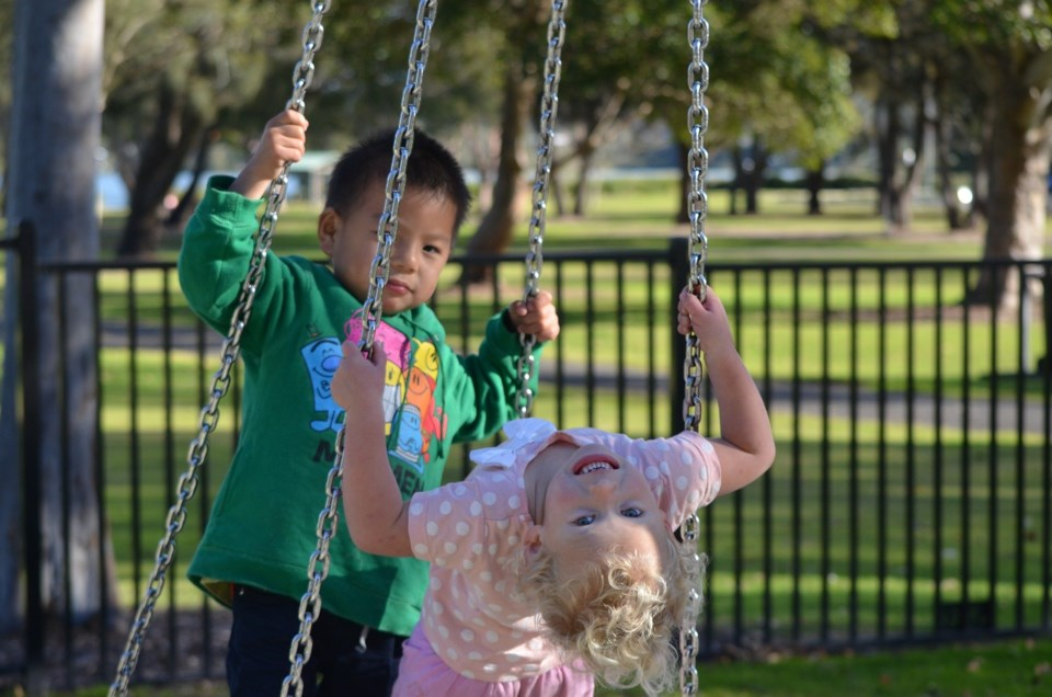 Two kids on swings on playground