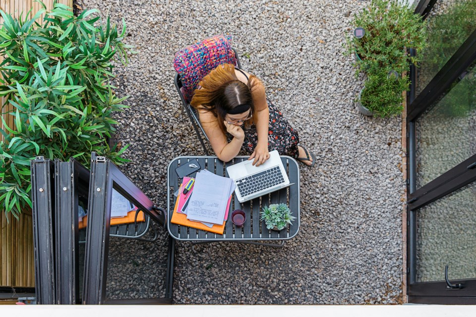 Student working at a table in a garden