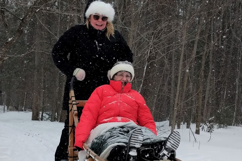 Jaime Robertson, sales and marketing manager for The Elden, drives a dog sled, while Elden resident Betty Maddocks gets a ride. Submitted photo