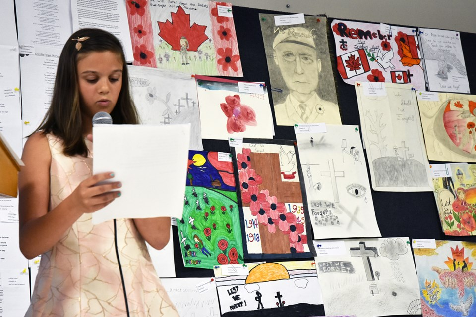 Sofia Marano reads her winning poem at the Bradford legion, against a backdrop of remembrance posters, essays and poems. Miriam King/Bradford Today