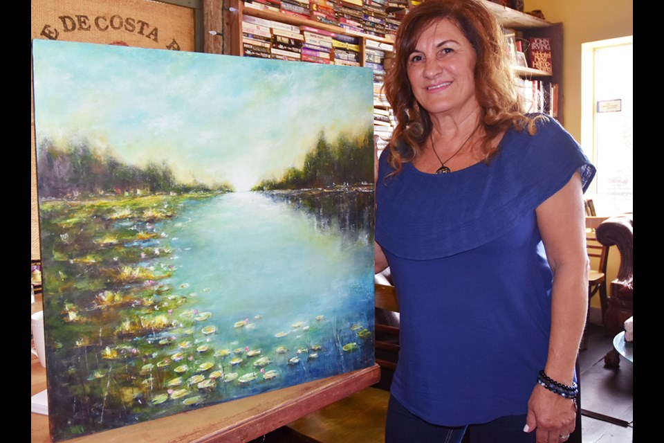 Artist Sylva Sroujian with oil and cold wax painting, 'Tranquil.' Miriam King/Bradford Today