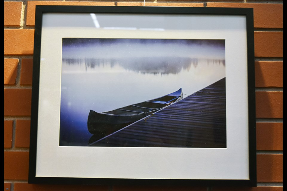Brooding photo of a canoe in the mist, by Jim Craigmyle - on exhibit at the Lakeshore Branch of the Innisfil idea Lab and Library. Miriam King/Bradford Today