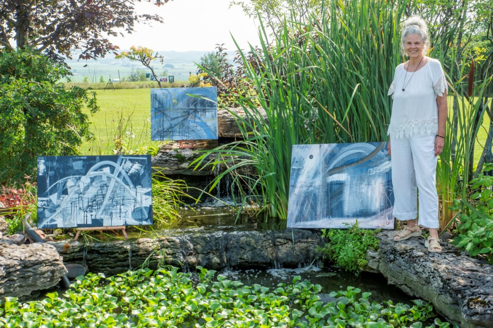 Artist Karen Lee stands with her works for the filming of the Passion Made video