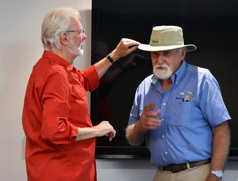 Alex Tilley, left, adjusts a Tilley hat for Rotarian Al Gilchrist, at the Aug. 15 Innisfil Rotary Club meeting. Miriam King/BradfordToday