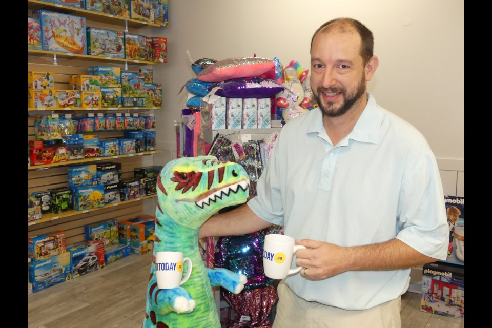 Experience Toys and Games co-owner Brian Hayden and a prehistoric pal.  Jenni Dunning/BradfordToday