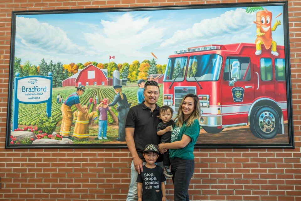 The Chang family stand inside the BWG Fire mural in their new restaurant. Paul Novosad for Bradford Today.