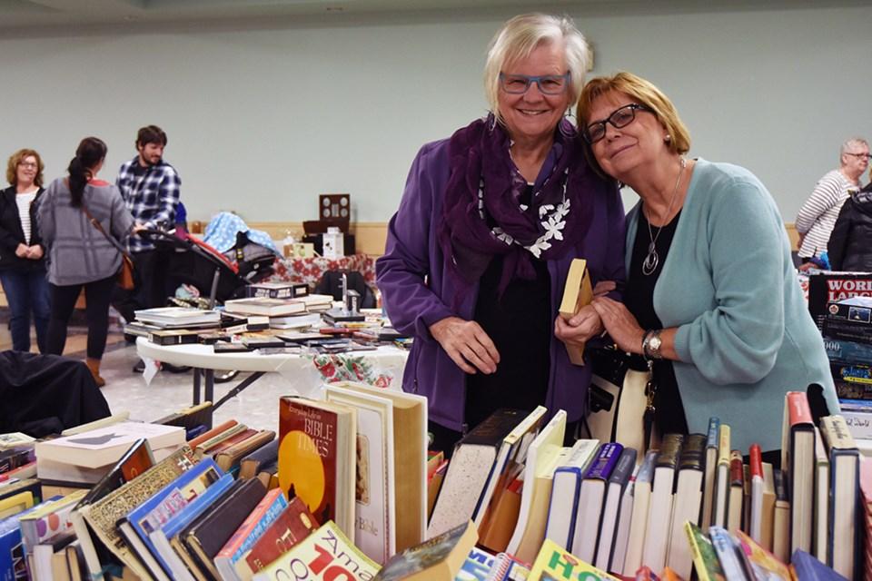 Mikki Nanowski, right, and Richardis Bianchi at the Used Book Table at the CWL Bazaar. Miriam King/Bradford Today