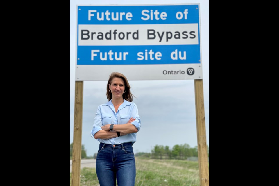 Minister of Transportation Caroline Mulroney in front of one of the new signs along the proposed route for the Bradford Bypass. She is defending her government's decision to forego an environmental assessment.
