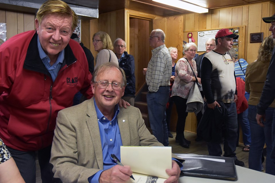 Author Dan Needles signs his book True Confessions from the Ninth Concession, for New Tecumseth Mayor Rick Milne. Miriam King/Bradford Today