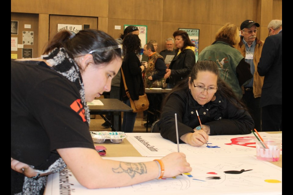 Artist Christi Belcourt painting one of her water protector stencils with a volunteer. Submitted photo/Anna Bourgeois