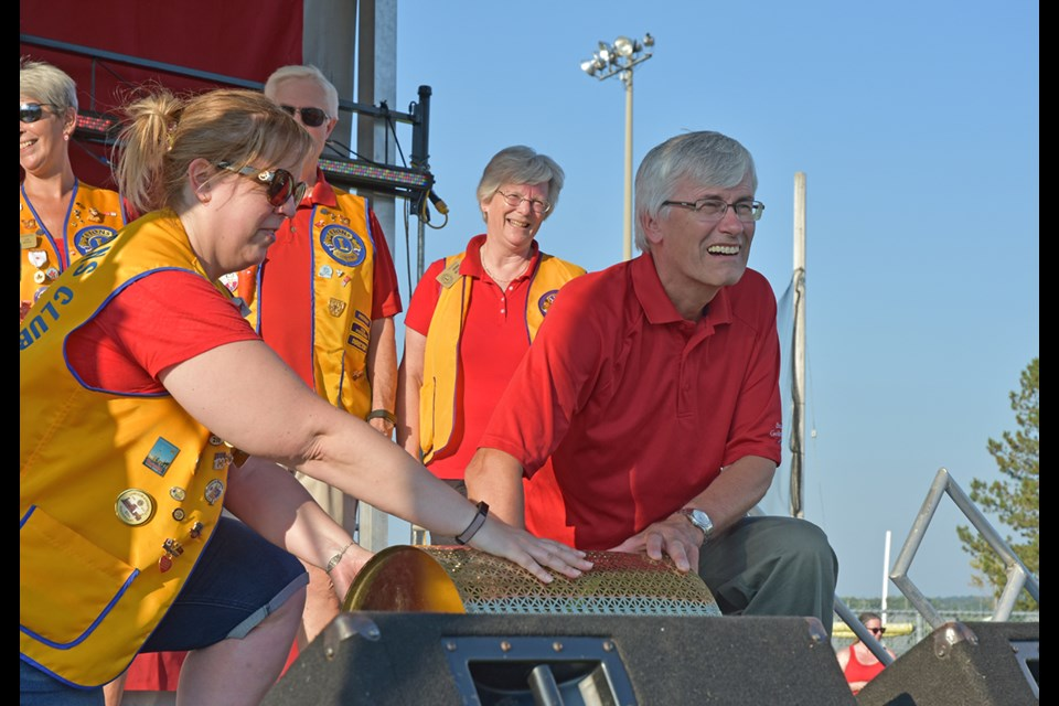 Surrounded by Bradford Lions Club members, Mayor Rob Keffer draws the first early-bird winner from a drum at Canada Day celebrations on July 1. Miriam King/Bradford Today
