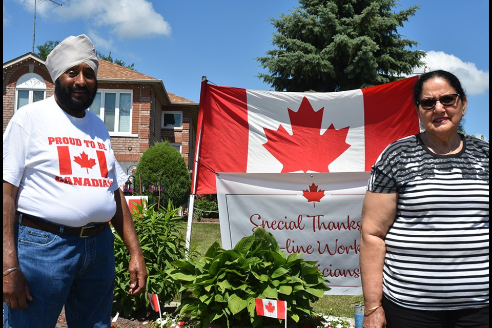 Darshan Singh Bilkhu and wife Nirmal stand beside Darshan's annual Canada Day display, at their Bradford home. Miriam King/Bradford Today
