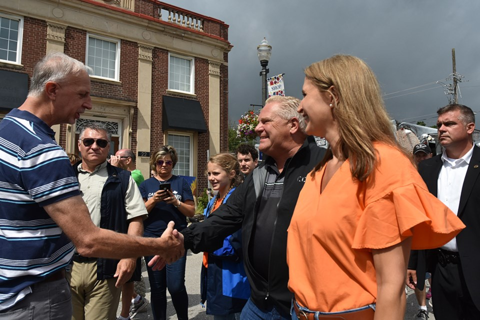 Minister of Transportation Caroline Mulroney, right, and Ontario Premier Doug Ford talk with constituents at Carrot Fest in Bradford, Aug. 17. Miriam King/Bradford Today