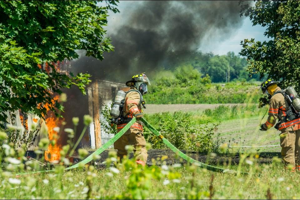 Bradford Fire pull hose out to extinguish a storage shed fire. Paul Novosad for BradfordToday.