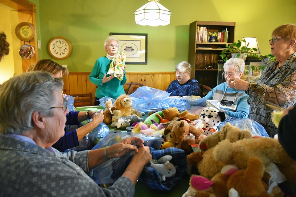 Leila Lloyd, president of the Bond Head Women's Institute (centre) demonstrates how to wrap a stuffed animal in a blanket, to an assembly line of women. Miriam King/Bradford Today