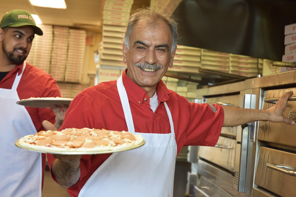 Serving up medium pepperoni pizzas at Pizza Nova, to raise money for Variety Village. Miriam King/Bradford Today