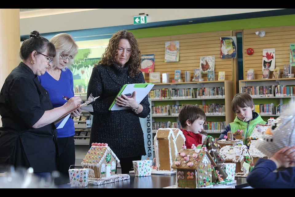 From left, Judges Beatriz Muller, Anne Kell and Sydney Hardie check out the entries in the Innisfil Rotary Club's Gingerbread House contest. SUBMITTED