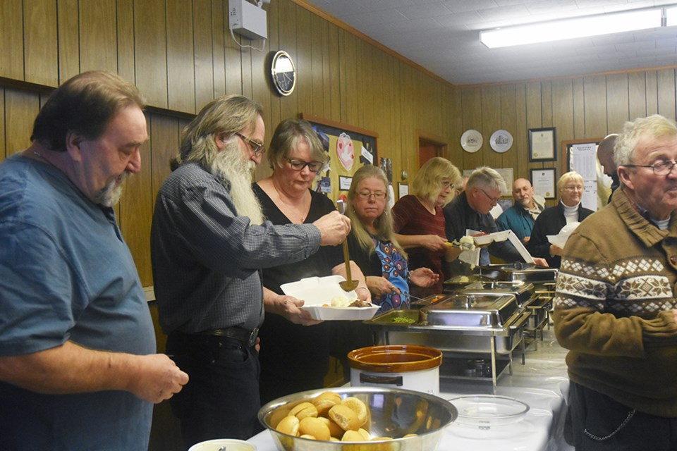 Line of volunteers serve up roast beef and all the trimmings, at Gilford United Church. Miriam King/Bradford Today