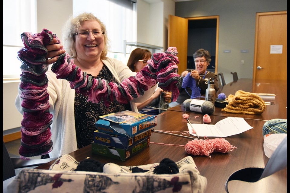 Nina Cunniff holds up a knitted scarf, at Knit Happens. Miriam King/Bradford Today