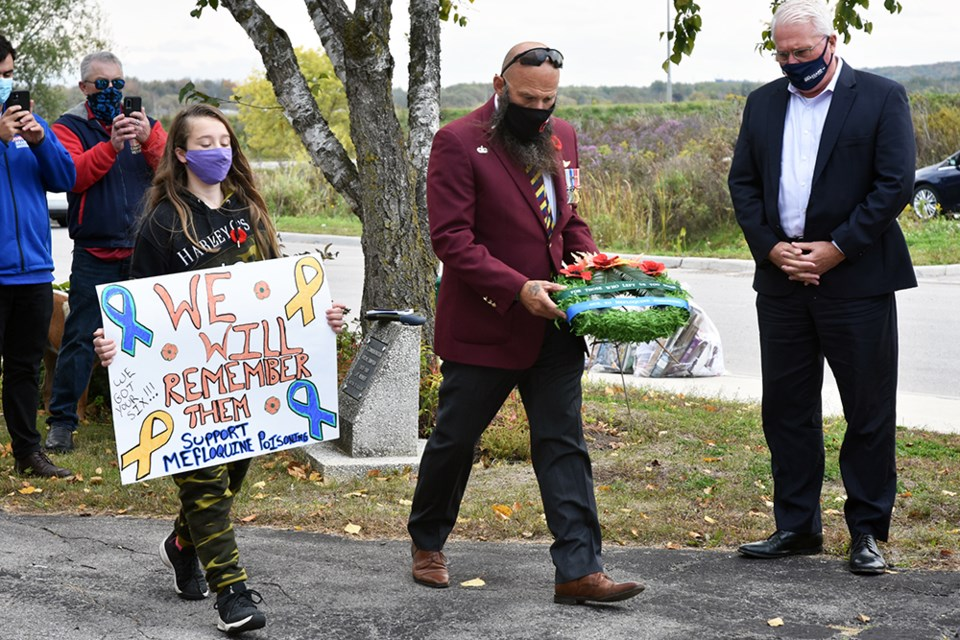Sgt. Mike Rude (Ret.) prepares to lay a wreath at the Bradford Legion, accompanied by Cpl. Brooklynn St. John, carrying poster. Miriam King for Bradford Today