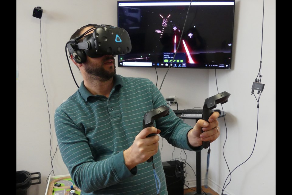 Brian Hayden, co-owner of Experience Toys and Games in downtown Bradford, plays virtual-reality game Space Pirate Trainer, shooting objects out of the sky. Jenni Dunning/BradfordToday