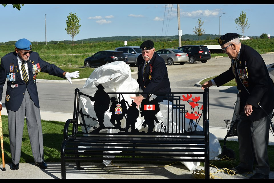 Veteran in U.N. Peacekeeping G. Michael Comeau, from left, Legion Service Officer George Neilson and Second World War veteran Bert Hogg unveil the veterans bench at the Bradford legion. Miriam King/Bradford Today