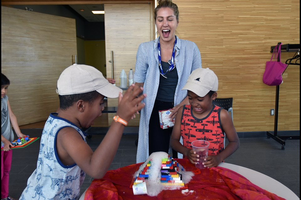 Andrea Ciurria, children's services librarian, with seven-year-old twins Jacob and Owen, creating a mega-eruption in Owen's LEGO volcano. Miriam King/BradfordToday