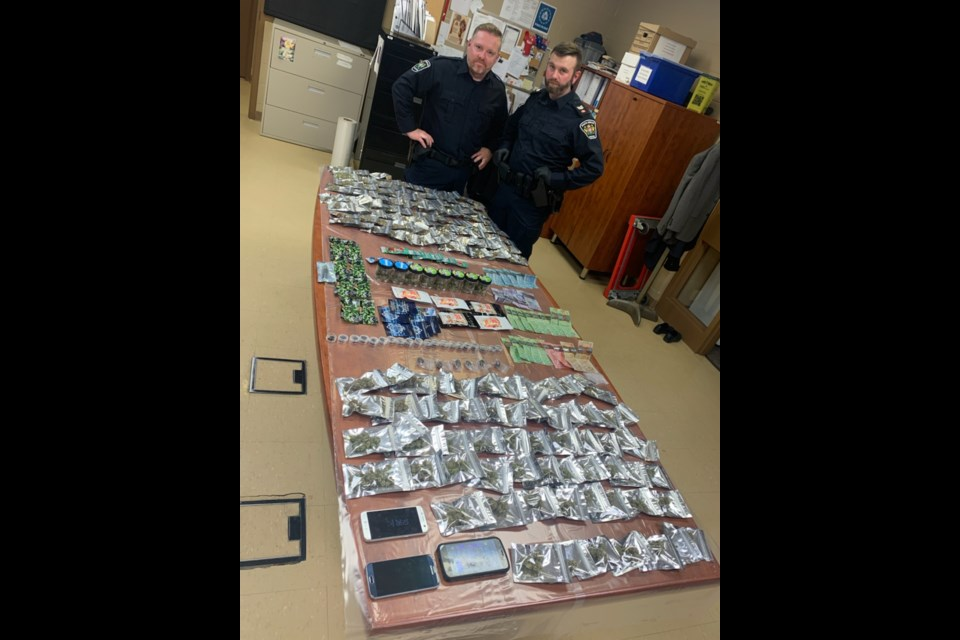 Simcoe Police Sgt. Dave Phillips and Const. Rob Griffin with the seized drugs — multiple individual packaged amounts of marijuana, cannabis edibles, hashish and shatter, a cannabis concentrate. Supplied photo/South Simcoe Police
