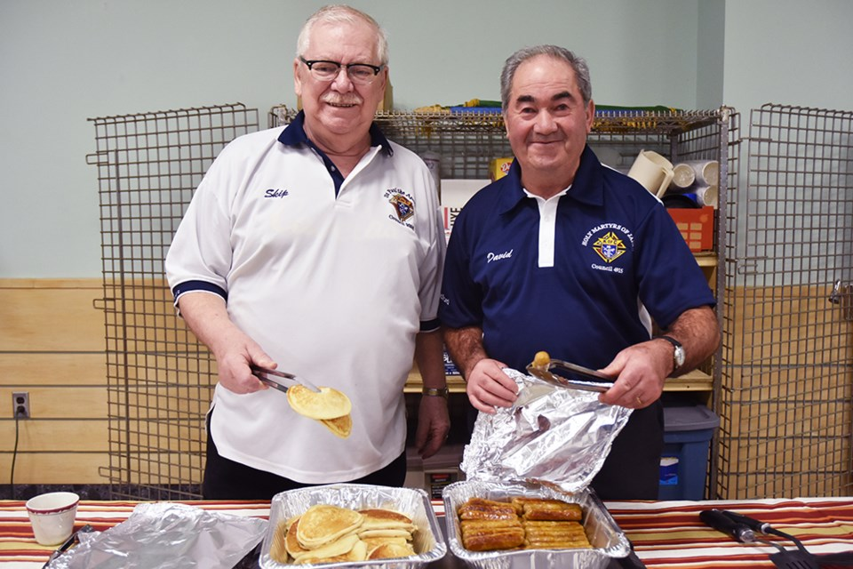 Knights of Columbus, T. (Skip) Langevin - TDA-N Zone Chair, at left, and David Oliebra serve up pancakes and sausages at Holy Martyrs of Japan Catholic Church. Miriam King/Bradford Today