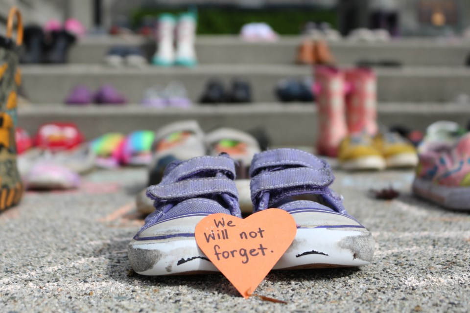 A display of children's shoes on the steps in front of the New Westminster cenotaph pays tribute to the 215 children whose bodies were found last week on the grounds of the former Kamloops Indian Residential School.