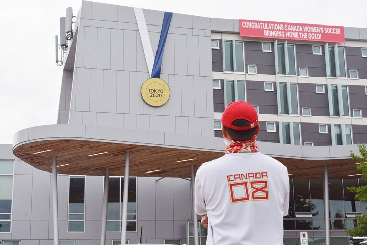 An onlooker eyes a giant medal hung in honour of Christine Sinclair.